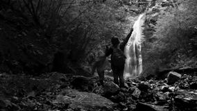 Black and white footage: mother and son climbing their way up to the waterfall in the twilight stock video footage