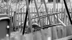 Black and white footage shot of deserted old abandoned ghetto playground swings. video stylized as old movie stock video footage