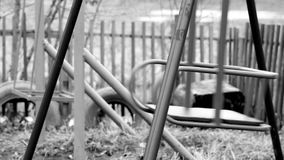 Black and white footage shot of deserted old abandoned ghetto playground swings. video stylized as old movie stock footage