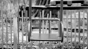 Black and white footage shot of deserted old abandoned ghetto playground swings. video stylized as old movie stock video