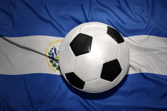 Black and white football ball on the national flag of el salvador Royalty Free Stock Images