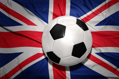Black and white football ball on the national flag of great britain Stock Image