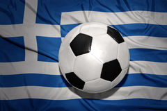 Black and white football ball on the national flag of greece Royalty Free Stock Photography
