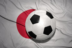 Black and white football ball on the national flag of japan royalty free stock images