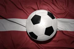 Black and white football ball on the national flag of latvia Royalty Free Stock Photo