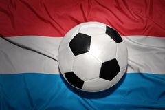 Black and white football ball on the national flag of luxembourg Stock Photography