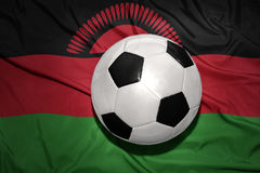 Black and white football ball on the national flag of malawi Stock Photography