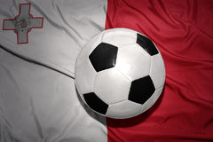 Black and white football ball on the national flag of malta. Vintage black and white football ball on the national flag of malta Royalty Free Stock Photo