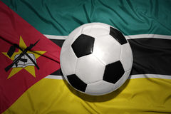 Black and white football ball on the national flag of mozambique Stock Photos