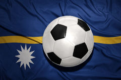 Black and white football ball on the national flag of Nauru Royalty Free Stock Images