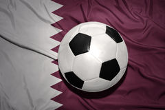 Black and white football ball on the national flag of qatar Royalty Free Stock Photos