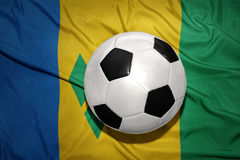 Black and white football ball on the national flag of saint vincent and the grenadines. Vintage black and white football ball on the national flag of saint Royalty Free Stock Photo