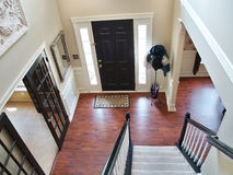 Black and White Foyer. A view down a stairway in a modern american home. Carpeted stairs and a wooden banister and railing are visible, and there is a hatstand Royalty Free Stock Photography