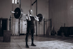 Black and white full length portrait of Strong man lifting a barbell during crossfit workout at gym royalty free stock images
