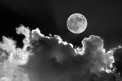 Black and white of full moon in night sky with dreamy moonlit clouds stock images