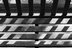 Black and white garden wooden bench with day light and shadow Royalty Free Stock Image
