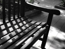 Black and white  garden wooden bench with day light and shadow Royalty Free Stock Photo
