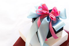 Black and white gift box with blue and pink ribbon bow Stock Photo