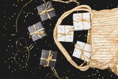 Black and white gift boxes with gold ribbon pop out from golden bag. On shine background. Flat lay stock photography