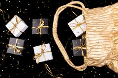 Black and white gift boxes with gold ribbon pop out from golden bag on shine background. Flat lay. Black and white gift boxes with gold ribbon pop out from Stock Images