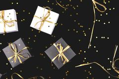 Black and white gift boxes with gold ribbon on shine background. Flat lay. Copy space royalty free stock image