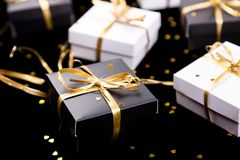 Black and white gift boxes with gold ribbon on shine background. Close up. Black and white gift boxes with gold ribbon on shine background. Close up Royalty Free Stock Photo