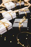 Black and white gift boxes with gold ribbon on shine background. Close up stock photography
