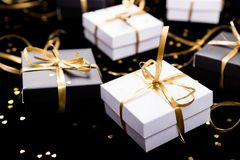 Black and white gift boxes with gold ribbon on shine background. Close up. Black and white gift boxes with gold ribbon on shine background. Close up Stock Photography