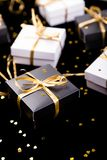 Black and white gift boxes with gold ribbon on shine background. Close up. Black and white gift boxes with gold ribbon on shine background. Close up Royalty Free Stock Photos