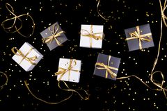 Black and white gift boxes with gold ribbon on shine background. Flat lay. Black and white gift boxes with gold ribbon on shine background. Flat lay Stock Image