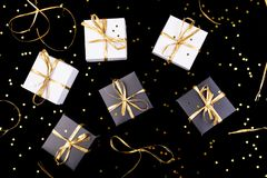 Black and white gift boxes with gold ribbon on shine background. Flat lay. Black and white gift boxes with gold ribbon on shine background. Flat lay Royalty Free Stock Photos