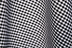 Black and white gingham checks. Black and white checks in a gingham fabric, draped to give a curvy, op art effect Stock Photos