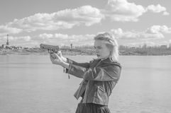 Black and white, girl aiming a pistol at the background of the l. Black and white, On a Sunny day a beautiful girl aiming a pistol Stock Image