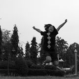 Black and white girl jumping happily. Black and white image of a girl jumping high happily in a garden  freedom Stock Photos