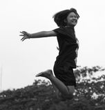 Black and white girl jumping happily. Black and white image of a girl jumping high happily in a garden  freedom Stock Image
