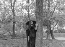 Black and white. Girl in mask and gown near the tree. The way to Halloween. The image of Halloween pretty Girl in a dress and a mask put his hand on the tree Stock Photos