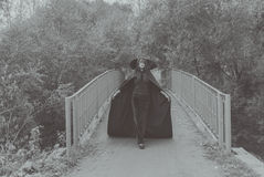 Black and white. The girl in the mask and mantle of the bridge on the Way to Halloween royalty free stock images