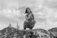 Black and white, in the girl`s hands a pistol, she`s sitting on. Black and white, girl with a pistol in hand sitting on a rock Stock Photography