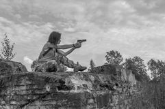 Black and white, in the girl`s hands pistol, she sits on a rock. Black and white, girl with a pistol in hand sitting on the wall Royalty Free Stock Image
