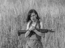 Black and white, the girl with the arms is on the field with gra. Black and white, in the girl`s hands the weapon is on the meadow Royalty Free Stock Photo