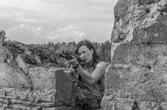 Black and white, in the girl`s hands the weapon she was aiming f. Black and white, girl with a gun in his hands aiming for the stone Royalty Free Stock Images