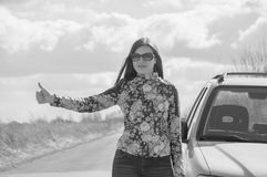 Black and white, girl stops the car, holding up a hand. Black and white, raising the thumb a beautiful girl stops the car Royalty Free Stock Photography
