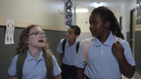 Black and white girls talk and laugh in school hall on the way to class.
