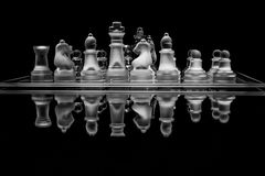 Black and white glass chess set with reflection stock images