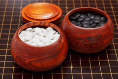 Black and white go stones in wooden bowls Royalty Free Stock Photo