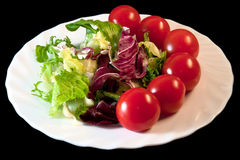 Black,white,green and red. Fresh green chopped salad with cherry tomatos on a white plate Stock Images