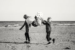Two funny Caucasian children kids with bunch of balloons playing running on beach stock photo