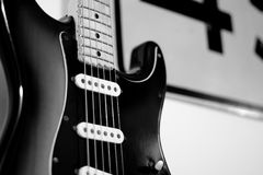 Black and white guitar. A partial black and white view of an authentic vintage six-string Fender Stratocaster guitar as it stands against a wall with a part of a Stock Photography