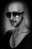 Black and white of hairless male in sunglasses looking at camera Royalty Free Stock Image