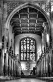 Black and White hall of a chapel. Ancient hall of a chapel in black and white hdr. Lonely archway is leading to the stained-glass window Royalty Free Stock Images
